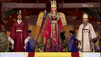 The ruler now, formerly Deokman to all, flanked by the heir apparent her nephew Kim Chunchu and the Dowager Queen, formerly Lady Maya.